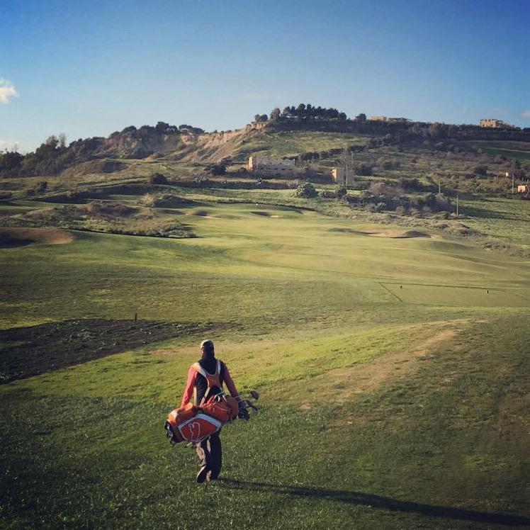 Me carrying my orange Puma golf bag in Italian countryside